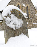 Snow-Covered Gravestone and Church